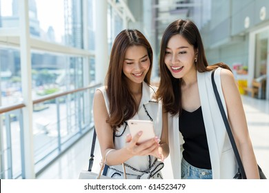 Two young girls go shopping together and using mobile phone