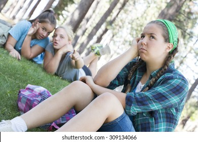 Two Young Girls Gossiping about another Girl