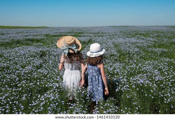 Two young girls in hats standing, holding hands in a flax field in Saskatchewan, Canada