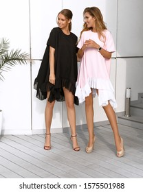 Two young girls having fun and relaxing together, prepearing for the party. Wearing pink and black dresses, high heel shoes. Volume hairstyle, bright makeup on face. Accessories, hot summer day