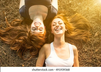 Two young girls having fun lying on the grass. Best friends smiling at the park in autumn. Concept about happiness, lifestyle and people