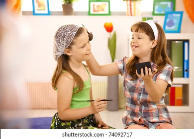 Two young girls having fun with makeup at home, smiling.?