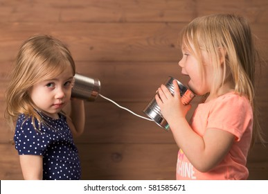 Two young girls having a tin can phone conversation