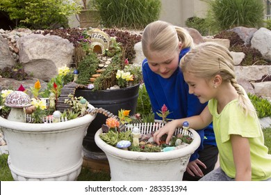 Two young girls helping to make fairy garden in a flower pot