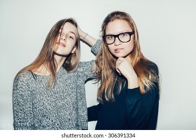 Two young girls hipsters teenagers friendly, very happy. friendship. Two pretty models smiling. Toned