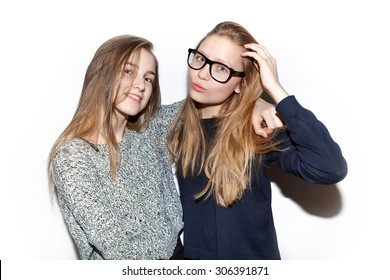 Two young girls hipsters teenagers friendly, cuddling, very cheerful and happy. Models smiling on white background, not isolated.