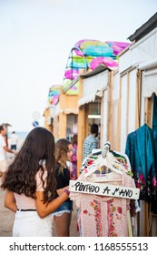 Two young girls look at a stall at an open-air market that has a sign that says the dresses are hand painted.
