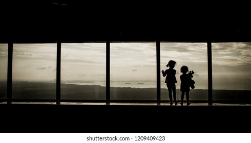 Two young girls looking out the high skyscraper window, panoramic view over the cityscape.