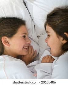 two young girls lying in the bed together