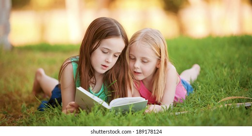 Two young girls lying on the grass outdoors reading a book.  These siblings are enjoying time together as family during summer