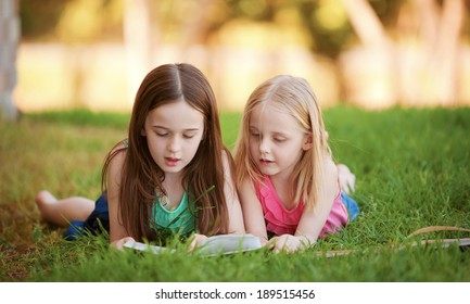 Two young girls lying on the grass outdoors reading a book.  These siblings are enjoying time together as a family during summer