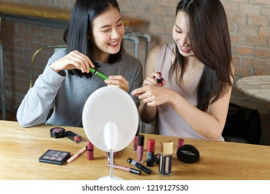 Two young girls making a video for their blog on cosmetics using a tripod mounted digital camera. They are testing new lipstick product. Young female blogger on camera screen holding cosmetics.