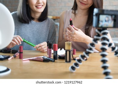 Two young girls making a video for their blog on cosmetics using a tripod mounted digital camera. They are testing new lipstick product. Seen in close up view. Cosmetic blogger product review concept.