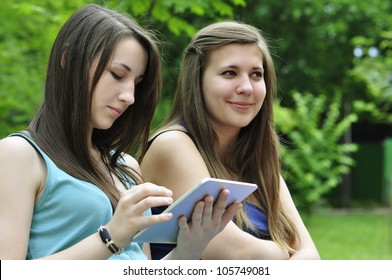 two young girls on bench using a tablet computer outdoor in park