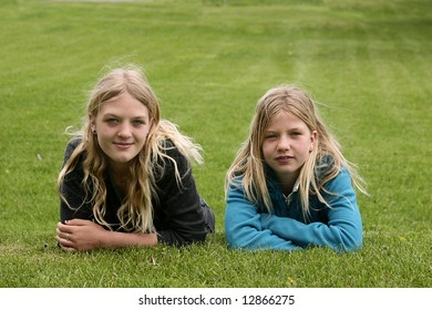 Two young girls on a grassy hill