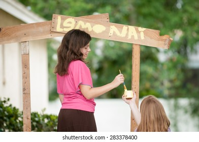 Two young girls painting a lemonade stand. One girl holds the container of yellow paint while the other girl paints the sign.