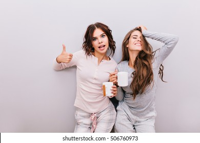 Two young girls in pajamas having fun on gray wall background. Girl with long hair laughing and keeps eyes closed, other with curly hair smiling to camera