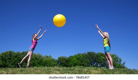 Two young girls play with big yellow ball in park