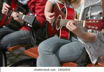 Two young girls playing acoustic guitar, real situation picture