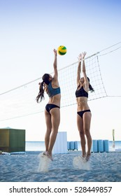 Two young girls playing beach volleyball during sunset or sunrise
