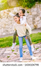 Two Young Girls Playing A Game Together At Sunny Day. Best Friends Having Fun In The Summer Riding each other's back. Young girl showing something.