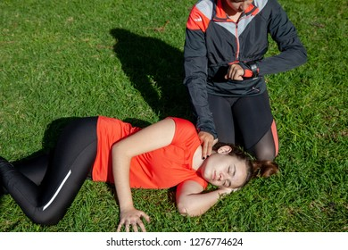 Two young girls practicing cardiopulmonary resuscitation manoeuvres in an open-air park