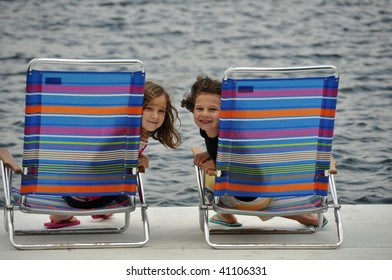 two young girls relax on a dock at the lake