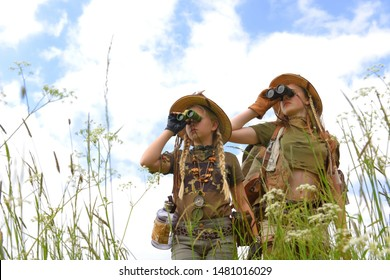 Two young girls seem to be on safari.They observe  the outdoor countryside area. They are dressed with  safari hats and khaki safari clothes.