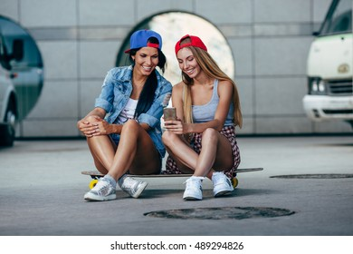 two young girls sitting on longboard