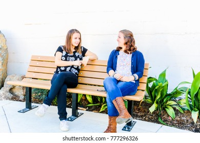 Two Young Girls Sitting on City Bench Together