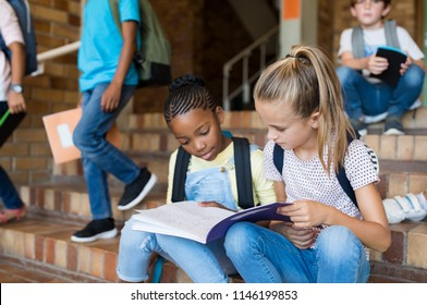 Two young girls sitting together on stairs after school. Elementary schoolgirls studying the notes on copybook. Happy african girl and her friend doing homework on notebook at primary school.