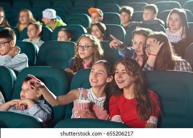 Two young girls smiling joyfully enjoying watching a movie together at the cinema friends friendship entertainment activity holidays weekend childhood happiness positivity comedy concept.