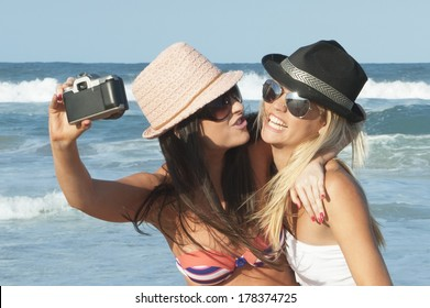 two young girls taking selfie  with film camera