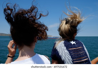 Two young girls with tousled hair, wind, look at a passing ship