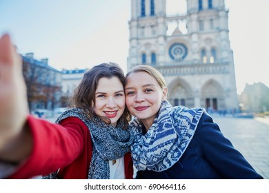 Two young girls walking together in Paris taking selfie with mobile phone near Notre-Dame cathedral. Tourism or friendship concept