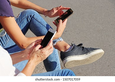 Two young girls watching smart mobile phones