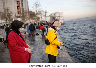 Two young girls are wearing mask and fishing on the Bosphorus Bridge in Istanbul, Turkey - December 09, 2020.
