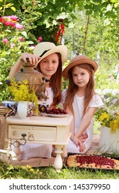 Two young girls in white dresses eat ripe cherries and drinking tea from an antique Russian samovar in the summer garden outdoors