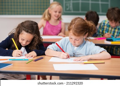 Two young girls working hard in class at school sitting side by side at a desk working on their projects