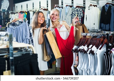two young glad women looking excited shopping new clothes in fashion market