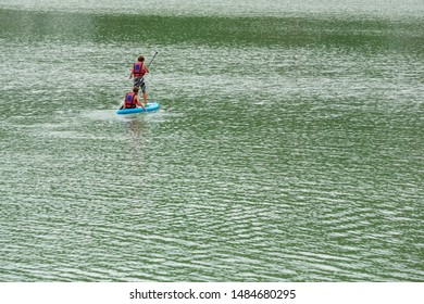 Two young guys are floating on a Board La sup surfing on the lake.