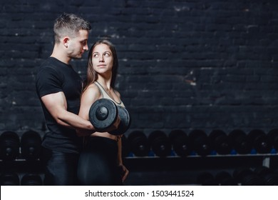 Two young guys and girls are engaged in the gym. During this time, they embracing themselves hold the weight in their hands while looking at each other.
