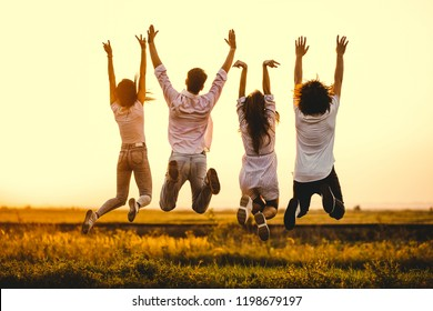 Two young guys and two girls are holding their hand and jumping in the field on a summer day. Back view.