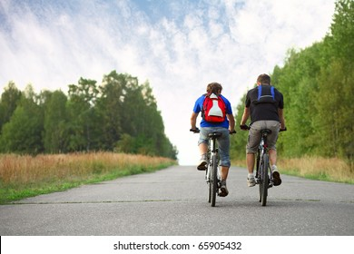 Two young guys on bicycles riding together on an asphalt road