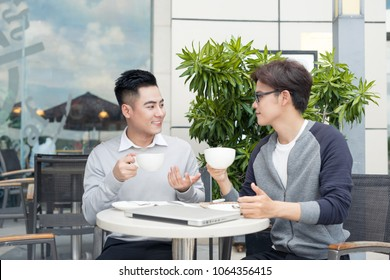 Two young handsome businessmen in casual clothes smiling, talking in coffee shop.