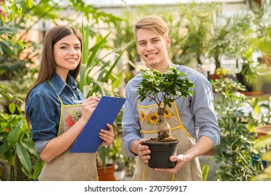 Two young handsome florists working at flowers shop. Looking at camera.