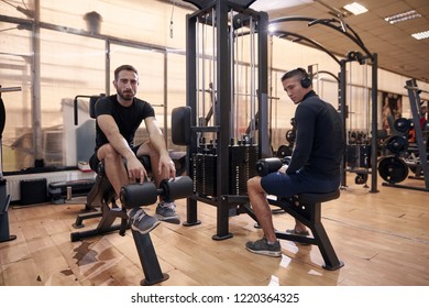 two young handsome man, 20-29 years old, posing in old gym indoors. fitnes equipment machines around them.