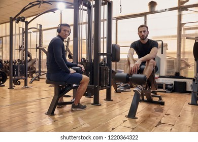 two young handsome man, looking to camera, 20-29 years old, posing in old gym indoors. fitnes equipment machines around them.