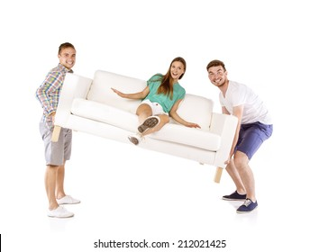Two young handsome men lifting sofa with young beautiful woman sitting on it, isolated on white background