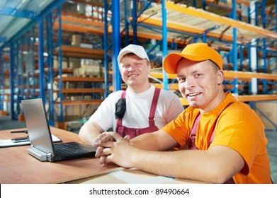 two young handsome workers man in uniform in front of warehouse rack arrangement stillages using notebook computer